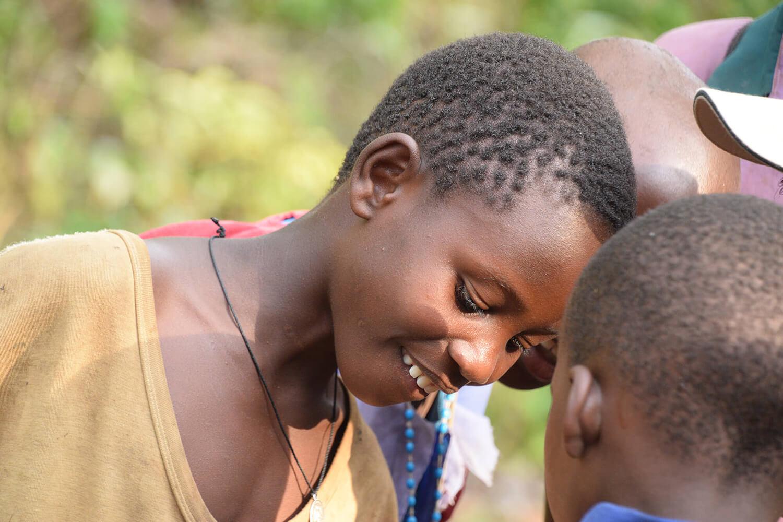 Reise in Uganda in Afrika. Eine einheimische Frau mit kurzen Haaren blickt lächelnd zu einem Kind herunter.