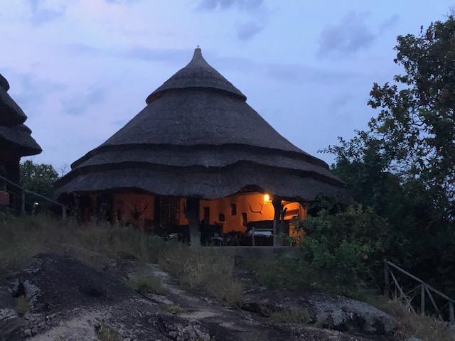 Reise in Uganda in Afrika. In einem Bungalow der Mihingo Lodge im Mburo Nationalpark brennt in Abenddämmerung Licht.