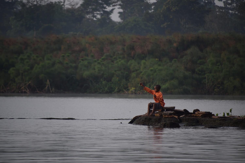 Reise in Uganda in Afrika. Ein einheimisches Kind sitzt am Ufer des Viktoria Sees und fängt Fische.