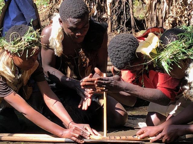 Reise in Uganda in Afrika. Angehörige des Batwa Stammes in traditioneller Kleidung zünden mit Brennstäben ein Feuer an.