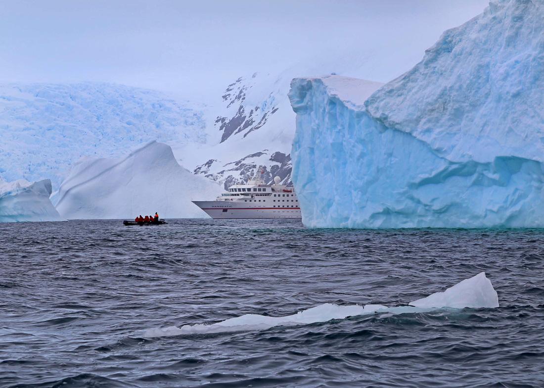 Reise in der Antarktis. Zwischen riesigen Eisschollen schwimmt das Expeditions Kreuzfahrtschiff MS Hanseatic von Hapag Lloyd Cruises, davor fährt ein Beiboot mit ein Paar Passagieren.
