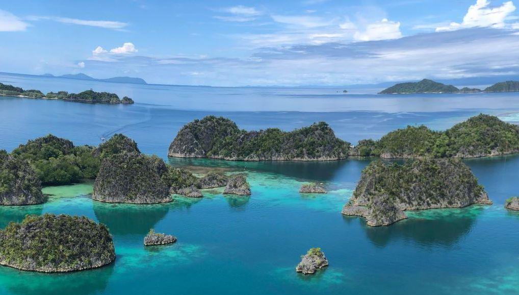 Reise in Raja Ampat in Indonesien. Aus der Luft blickt man auf das Archipel der üppig bewachsenen Faminseln im türkisen Meer.