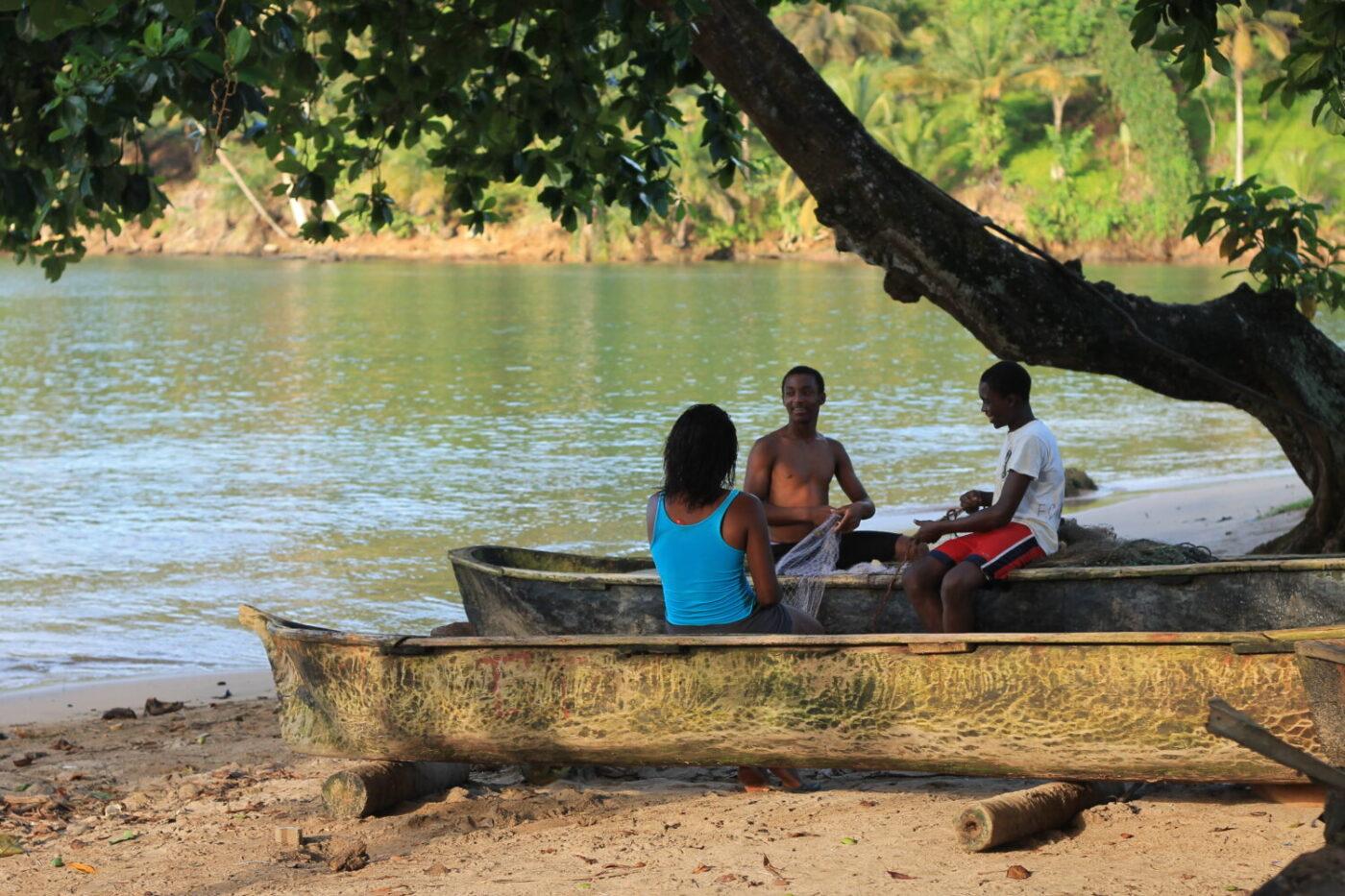 Reise in Sao Tome und Principe in Afrika. Drei junge Einheimische sitzen auf traditionellen Fischerbooten am Strand im Schatten eines grossen Baumes und flicken Fischernetze.
