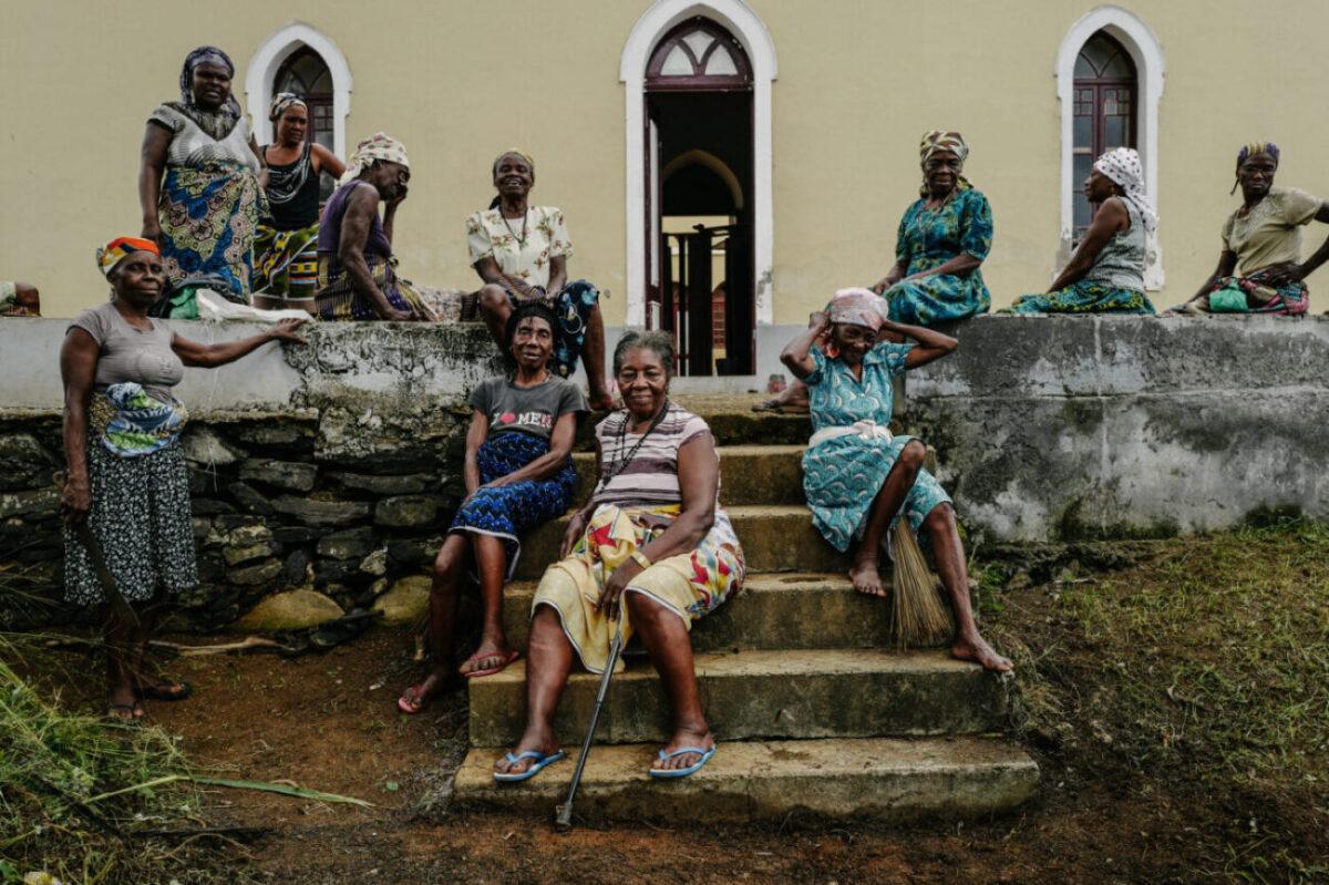 Reise in Sao Tome und Principe in Afrika. Elf alte, in bunte Tücher gekleidet, sitzen oder stehen auf der Treppe und einem Vorplatz eines grossen Gebäudes und blicken in die Kamera.