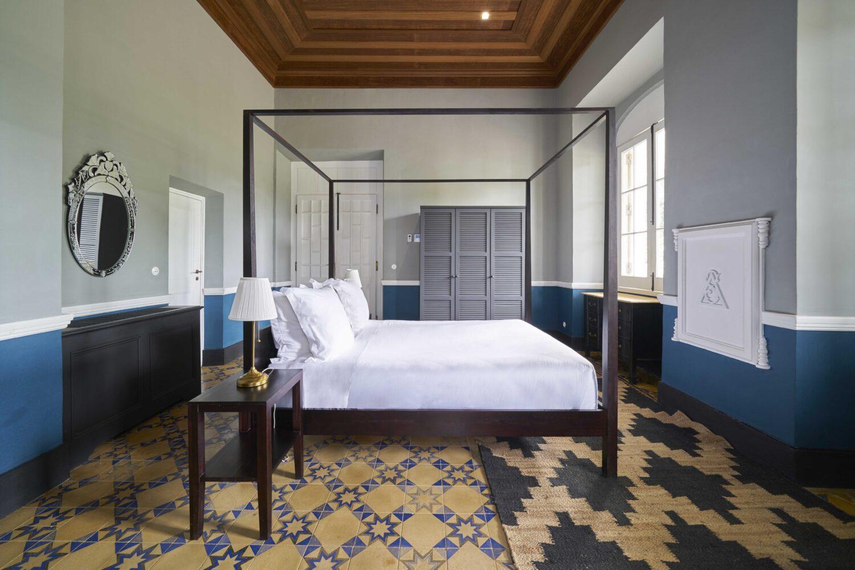 Reise in Sao Tome und Principe in Afrika. Ein Zimmer im Hotel Roca Sundy ist sehr stilvoll mit einem grossen Doppelbett aus dunkelm Holz und viel Stauraum eingerichtet.