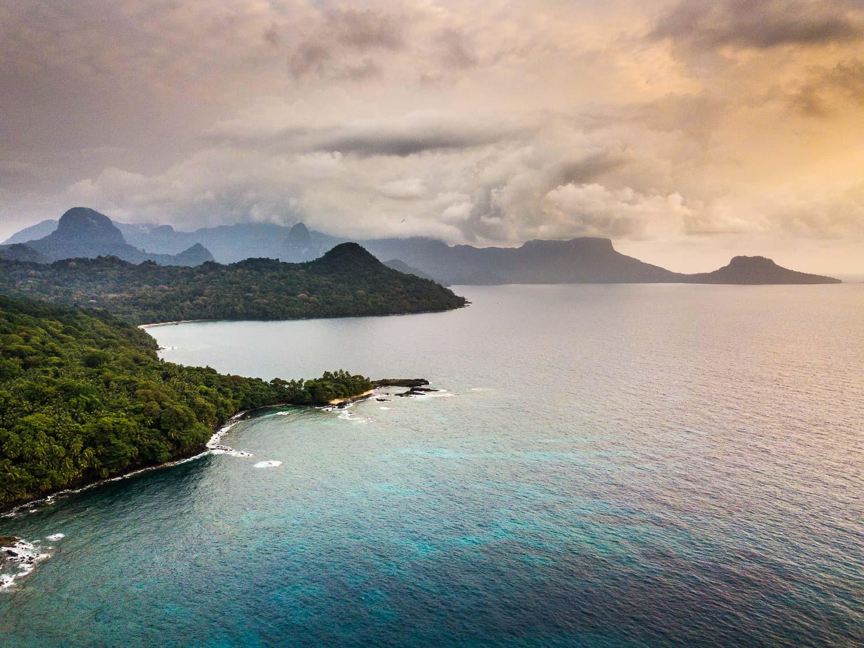 Reise in Sao Tome und Principe in Afrika. Ansicht auf die Insel aus der Luft, die Hügel sind von Regenwald bedeckt, markante Basaltnadeln ragen vereinzelt empor, Sandstrand umgibt die Küste der Insel, türkise Wellen brechen sich. Der Himmel ist bewölkt