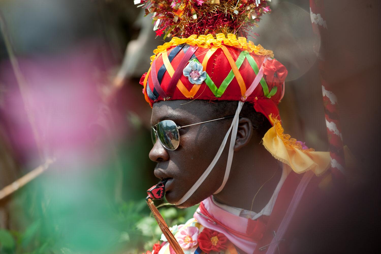 Reise in Sao Tome und Principe in Afrika. Ein einheimischer Mann trägt eine bunte Kopfbedeckung, eine Sonnenbrille und hat eine Trillerpfeife im Mund da er am traditionellen Karneval teilnimmt.