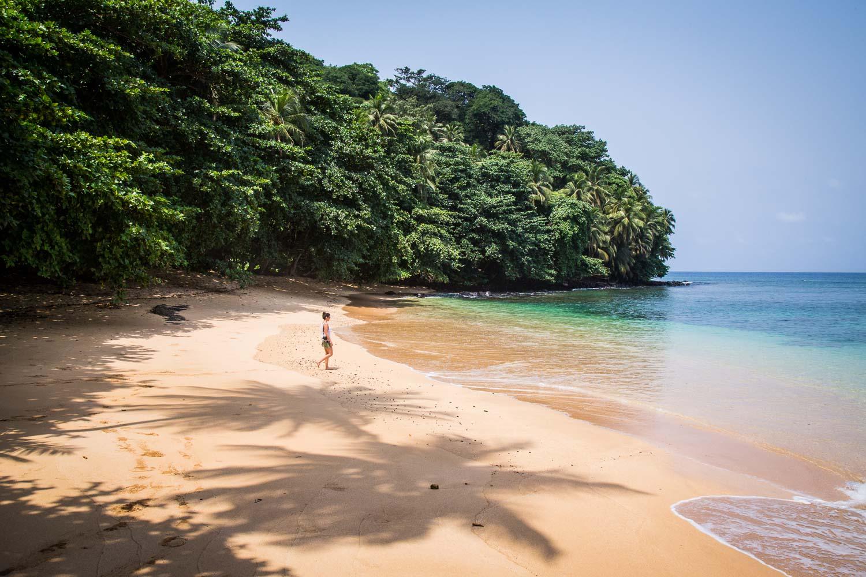 Reise in Sao Tome und Principe in Afrika. Direkt an den Urwald grenzt ein breiter Sandstrand, die türkisfarbenen Wellen brechen sich leicht am Strand, eine junge Frau läuft auf das Meer zu.