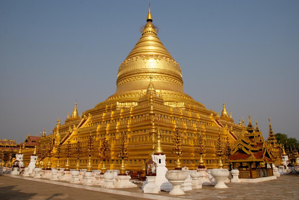 Reise in Myanmar in Asien. Die goldene Shwezigon Pagode in der Tempelstadt Bagan wird von der Abendsonne in warmes Licht getaucht.