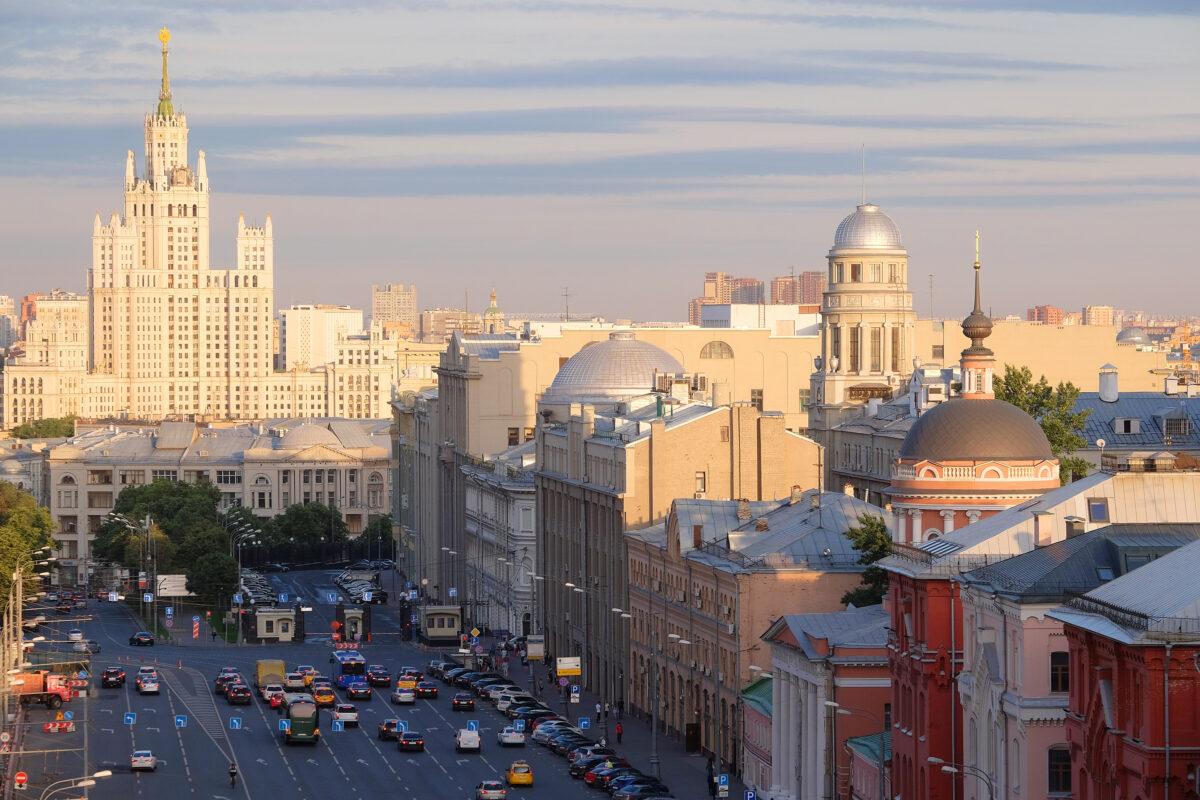 Reise in Russland in Europa. Am Abend Sicht auf die Metropole Moskau mit ihren historischen Gebäuden, im Feierabendverkehr stehen einige Autos.