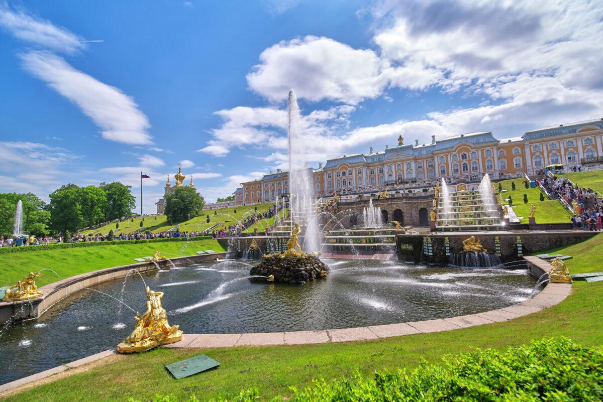 Reise in Russland in Europa. Der spektakuläre goldene Brunnen des Peterhof in St. Petersburg ist von einigen Besuchern umzingelt, im Hintergrund ragt der Palast auf.