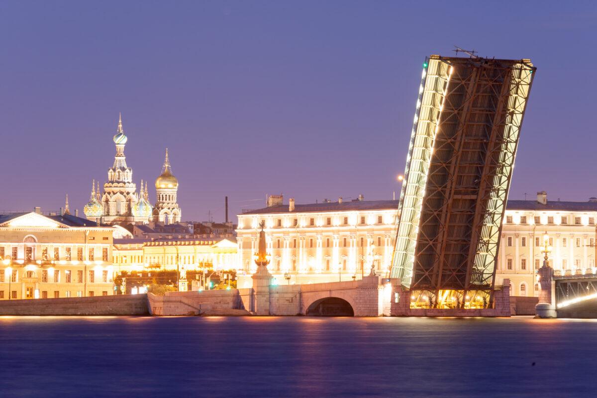 Reise in Russland in Europa. Die Troitsky Brücke im nächtlichen St. Petersburg ist hochgezogen, die Gebäude und Kuppeln sind hell beleuchtet.