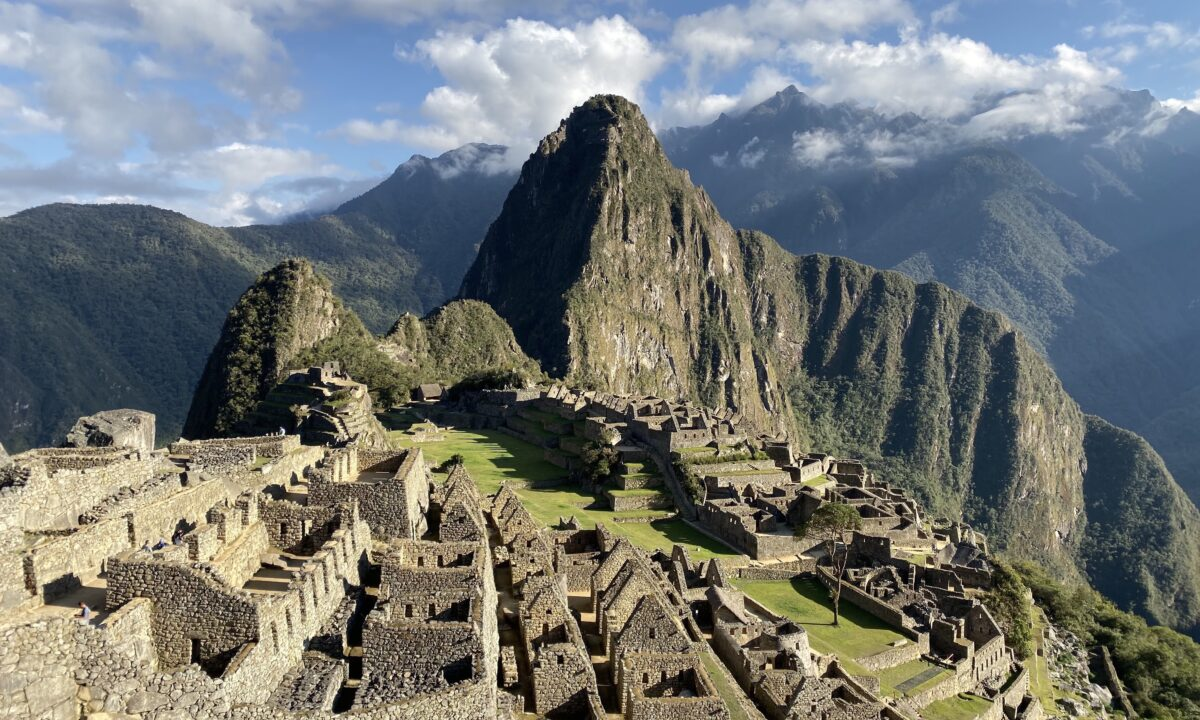 Simtis Reisevortrag Peru und Bolivien in Südamerika. Die Stadt Machu Picchu wird von der Morgensonne beschienen, die Ruinen werfen lange Schatten.