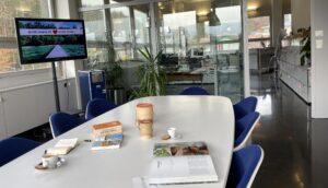 """Geräumiges Büro von Simtis Reisen weltweit, in Sitzungszimmer liegen Reiseführer, Karten, und ein Kaffee bereit, am Fernsehbildschirm steht der Schriftzug """"Reiseplanung mit Liebe zu den Details""""."""