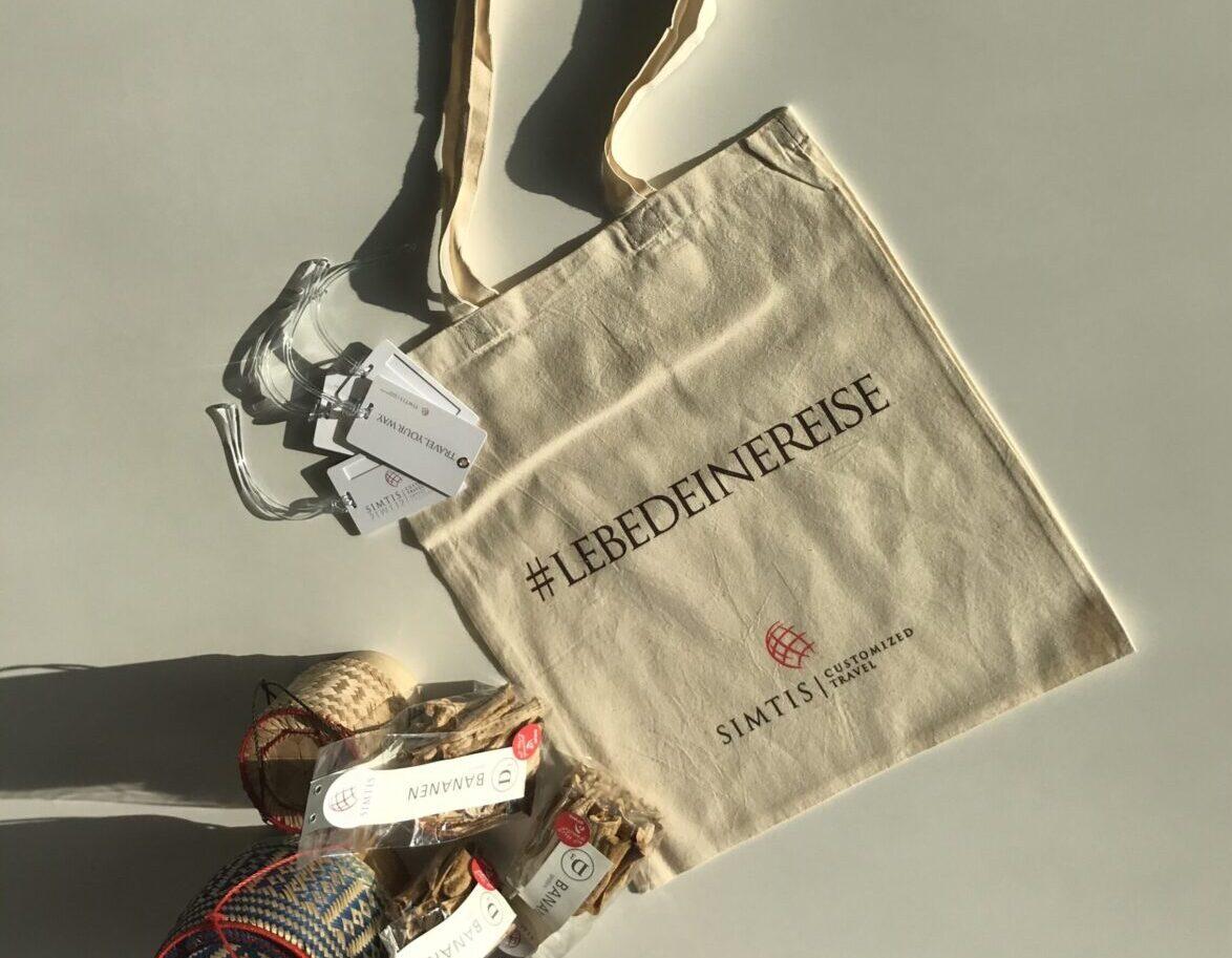 """Beispielbild. Simtis verschenkt Giveaways in Baumwolltaschen, die mit dem Hashtag """"Lebe deine Reise"""" bedruckt sind. Zusätzlich werden Trockenbananen aus dem Arwo Hilfswerk in Baden verschenkt, sowie Gepäckschilder mit Simtis Logo."""
