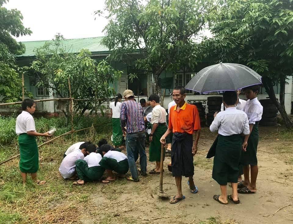 Soziales Projekt in Myanmar. Einige Freiwilliger pflanzt Bäume im Boden.