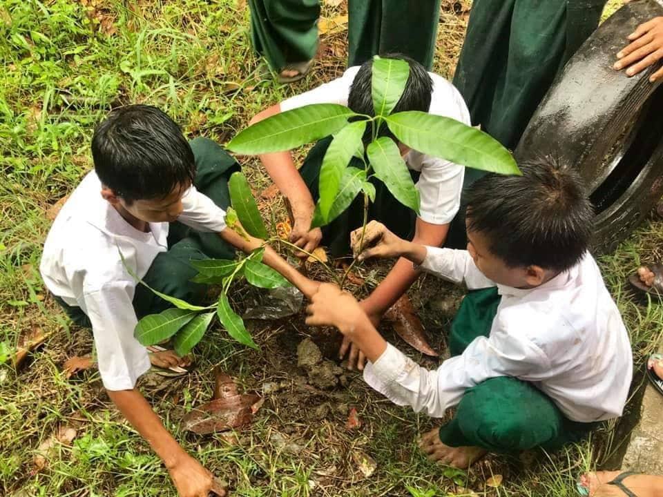 Soziales Projekt in Myanmar. Eine Gruppe Kinder pflanzt gemeinsam einen Baum.