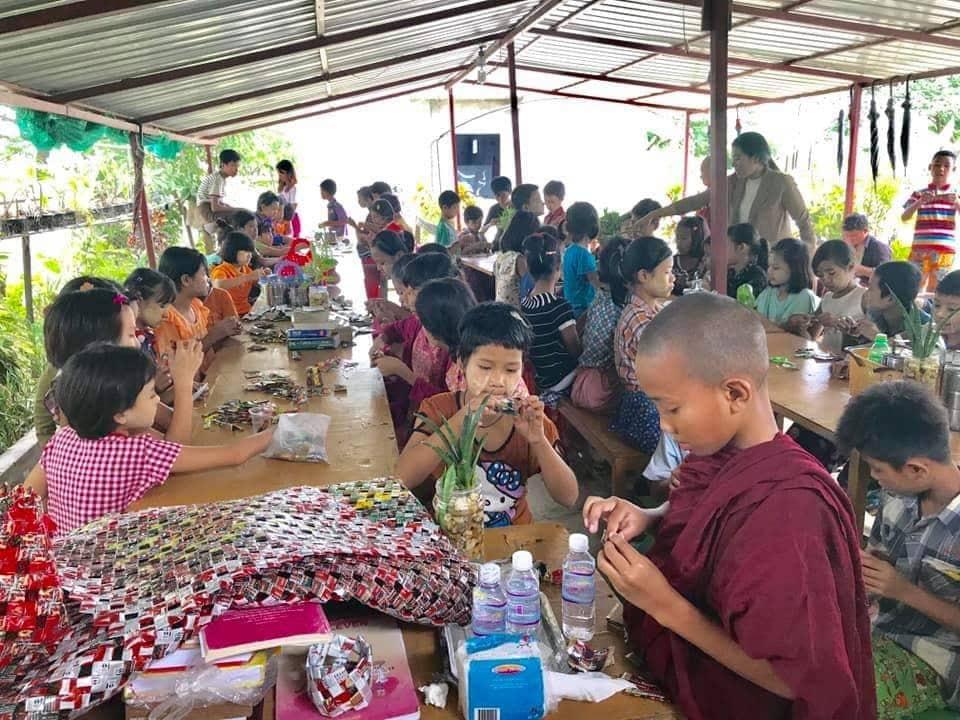 Soziales Projekt in Myanmar. Bei einer Schulkampagne lernen die Kinder, wie wichtig Recycling für die Natur ist. Kinder sitzen auf Schulbänken und basteln mit altem Plastik.