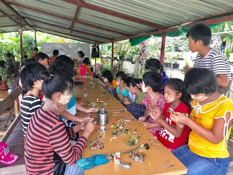 Soziales Projekt in Myanmar. Bei einem Schulprojekt lernen die Kinder, wie wichtig Recycling für die Natur ist. Kinder sitzen auf Schulbänken und basteln mit altem Plastik.