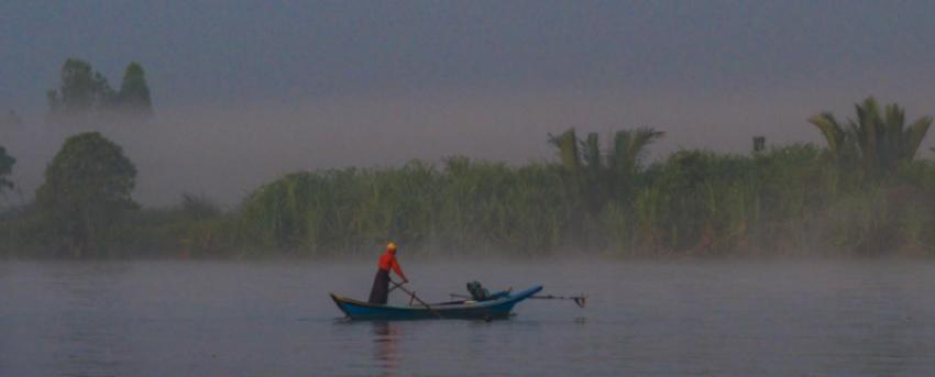 Reise in Myanmar in Asien. Stimmungsbild mit einem Fischer, der in der Morgendämmerung vor einem Schilf auf den Fluss rudert.