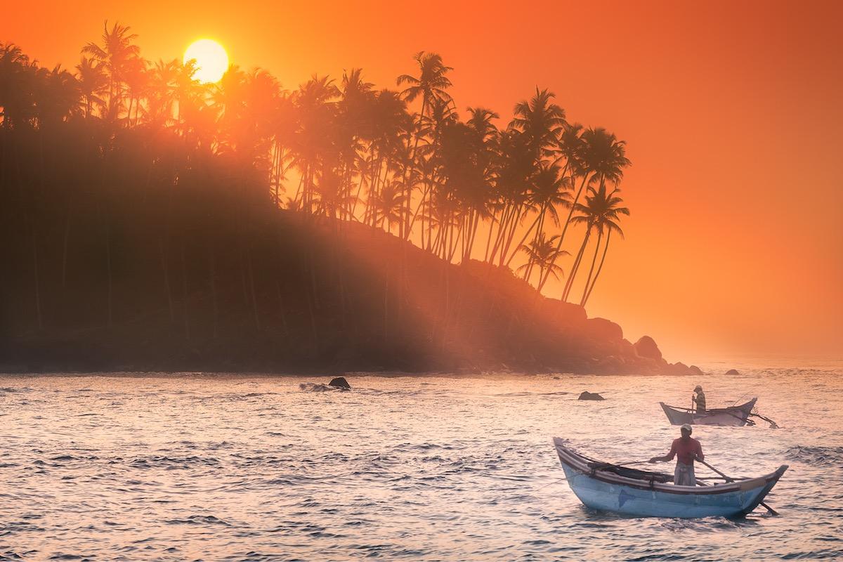 Reise in Sri Lanka in Asien. Stimmungsbild von Fischern, die kurz vor Sonnenuntergang an der Küste bei Mirissa ihre Netze auswerfen.