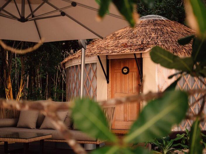 Reise in Myanmar in Asien. Ein stilvoller Holzbungalow des Awei Pila Resorts im Mergui Archipel ist von Dickicht umgeben, davor steht eine Sitzgruppe mit einem Sonnenschirm