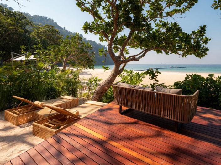 Reise in Myanmar in Asien. Auf einer Holzterrasse steht ein Sofa, im Strand daneben stehen zwei Liegestühle mit Sicht auf den Strand und das Meer beim Awei Pila Resort im Mergui Archipel.