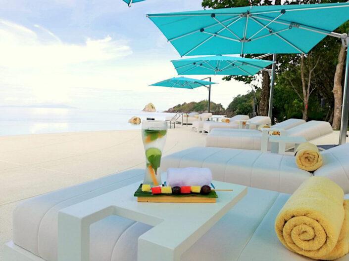 Reise in Myanmar in Asien. Auf einem Liegestuhl der Poolanlage des Awei Pila Resorts im Mergui Archipel liegen nebst einem Badetuch ein erfrischender Fruchspiess und ein kaltes Getränk.