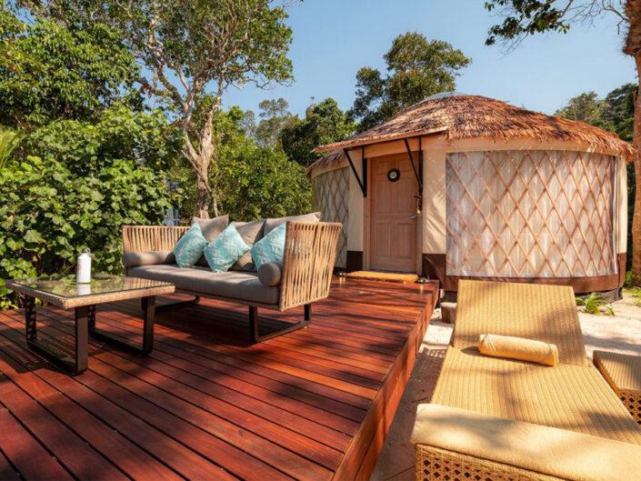 Reise in Myanmar in Asien. Vor dem runden Strandbungalow des Awei Pila Resorts im Mergui Archipel ist ein gedeckter Vorplatz angebracht mit einer Sitzgruppe und einem kleinen Tisch, im Sand daneben stehen zwei Liegestühle.