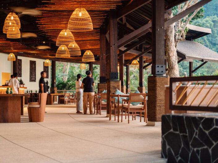 Reise in Myanmar in Asien. Die gedeckte Lobby des Awei Pila Resorts im Mergui Archipel ist stilvoll eingerichtet und bietet direkte Sicht auf die Poolanlage.
