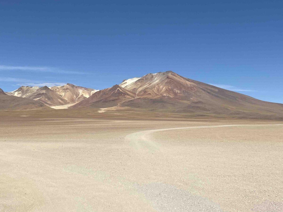 Reise in Bolivien in Südamerika. Hinter einer Wüste im Altiplano Hochland ragen die Anden empor.