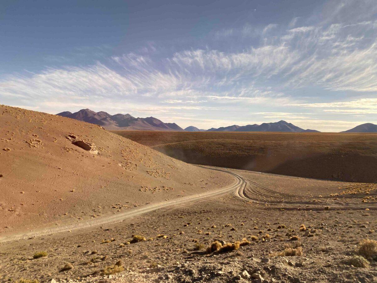 Reise in Bolivien in Südamerika. Bild von einer weiten, staubigen Ebene mit Autospuren im Altiplano Hochland, im Hintergrund erhebt sich das Anden Gebirge.