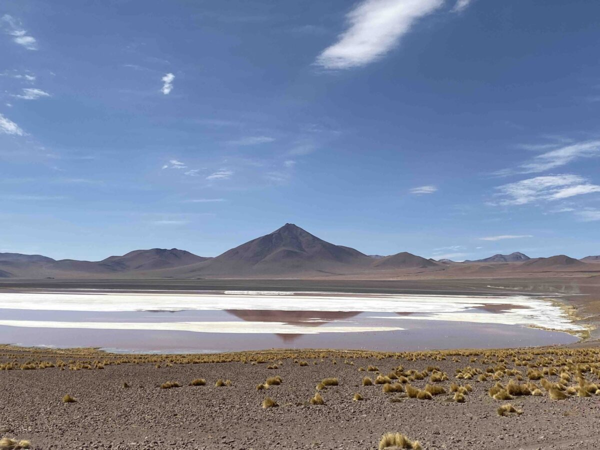 Reise in Bolivien in Südamerika. Naturbild vom Hochland Altiplano mit einem Salzsee vor der hohen Bergkette des Anden Gebirges.