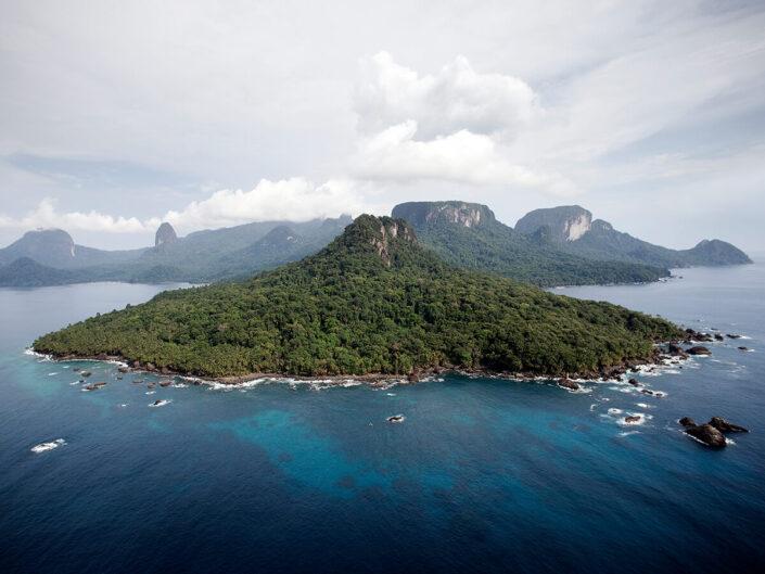 Reise in Sao Tome und Principe in Afrika. Blick auf die Insel Principe aus der Luft, man sieht dichten Urwald, hohe Berge und die Brandung entlang der Küste.
