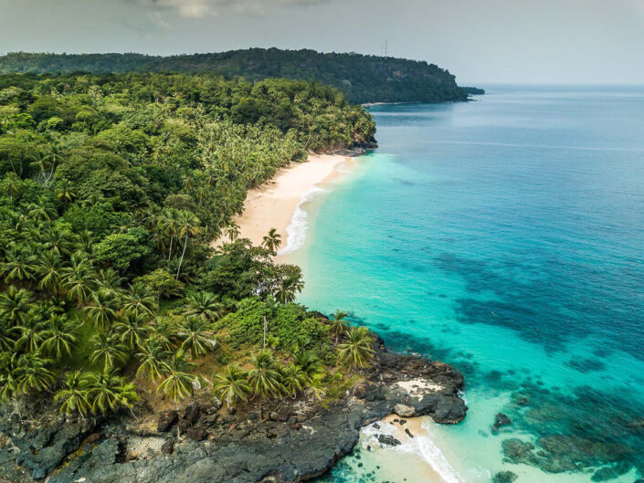 Reise in Sao Tome und Principe in Afrika. Blick auf die Insel Principe aus der Luft, man sieht hellen Sandstrand, das türkisfarbene Meer und zahlreiche Palmen.
