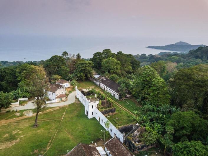 Reise in Sao Tome und Principe in Afrika. Aus der Luft blickt man auf das ehemalige, weisse Plantagenhaus des heutigen Hotels Roca Sundy herab. In der Ferne liegt hinter dem Urwald das Meer.