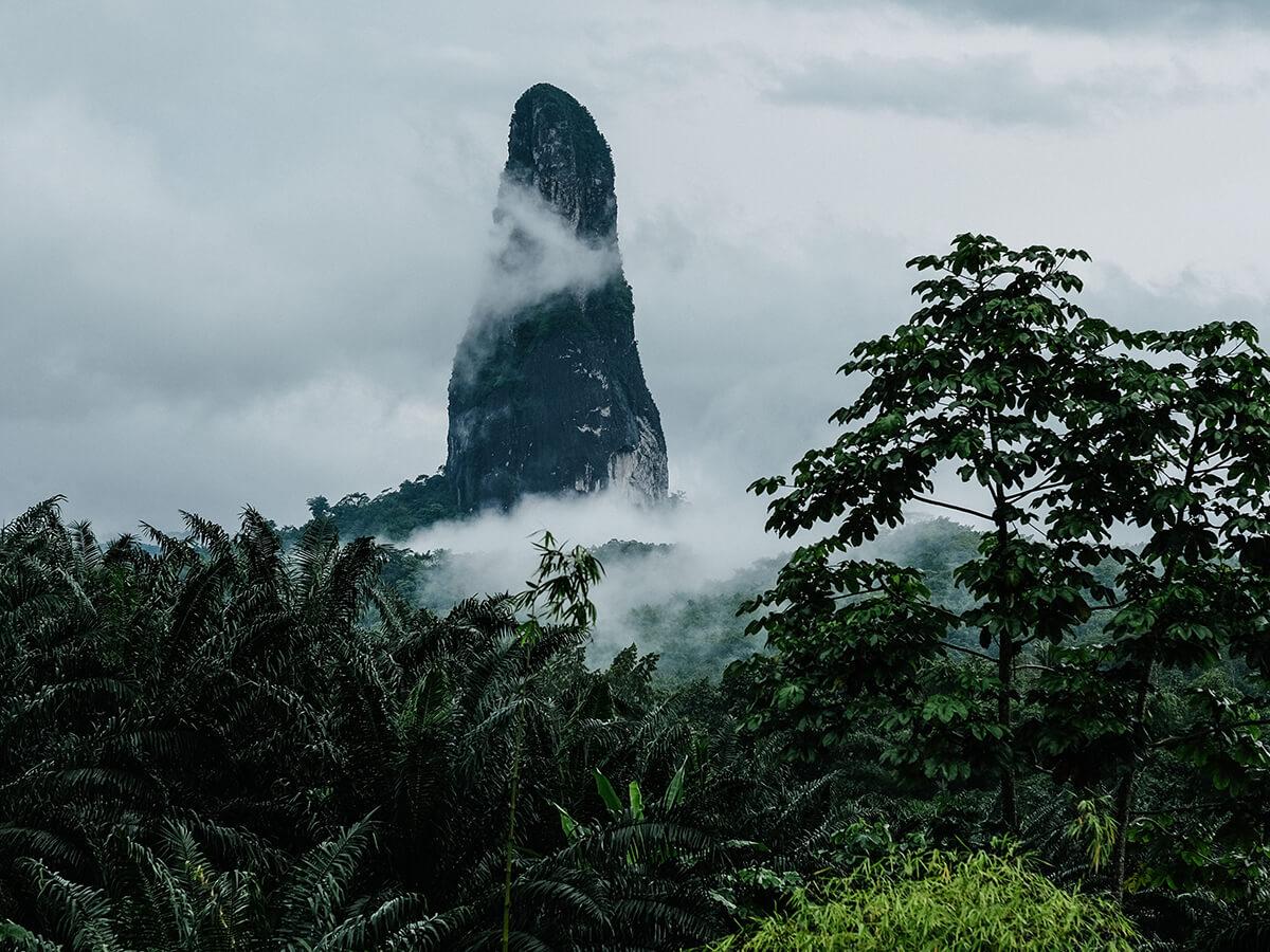Reise in Sao Tome und Principe in Afrika. Die Basaltnadel Pico Cao Grande ragt aus dem Urwald empor und wird von Dunst umgeben.