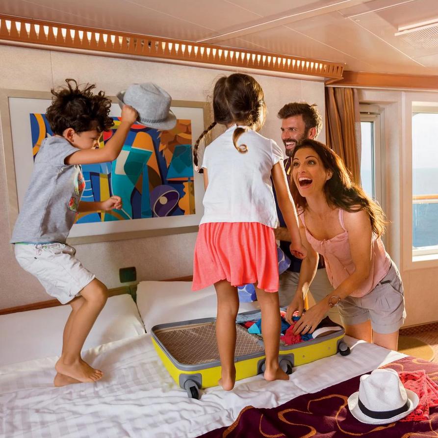 Eine Familie mit zwei Kindern packt in der Kabin eines Kreuzfahrtschiffs aus.