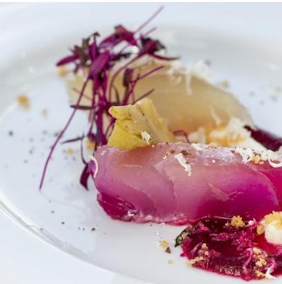 Eine kunstvoll angerichtete Speise wird auf einem weissen Teller serviert.