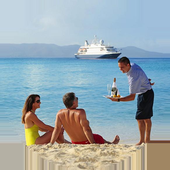 Ein Pärchen liegt am Strand, während ein junger Kellner sie mit Champagner bedient. Auf dem Meer ist ein Kreuzfahrtschiff zu sehen.
