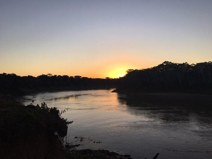 Reise in Peru in Südamerika. Stimmungsbild im Tambopata Naturreservat mit Fluss-und Waldlandschaft, während die Sonne untergeht