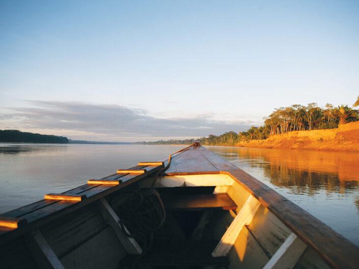 Reise in Peru in Südamerika. Blick von einem Kanu aus auf den Fluss und die bewaldeten Ufer des Tambopata Naturreservats, die von der aufgehenden Sonne beschienen werden.