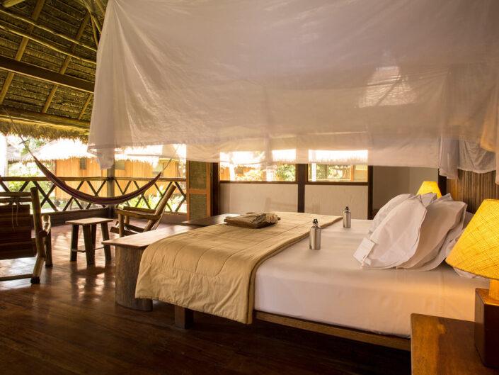 Reise in Peru in Südamerika. In einer Suite der Inkaterra Reserva Amazonica Lodge hat es ein komfortables Doppelbett, wiederbefüllbare Trinkflaschen aus Edelstahl, eine Hängematte und Sitzgelegenheiten. Von der offenen Terrasse aus blickt man mitten in den Amazonas Regenwald.