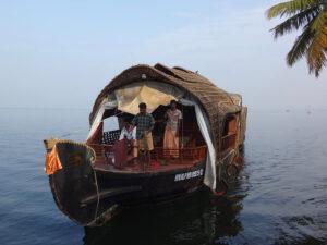Reise in Indien in Asien. Ein grosses Boot mit zwei Einheimischen an Bord fährt durch die Backwaters in Kerala.