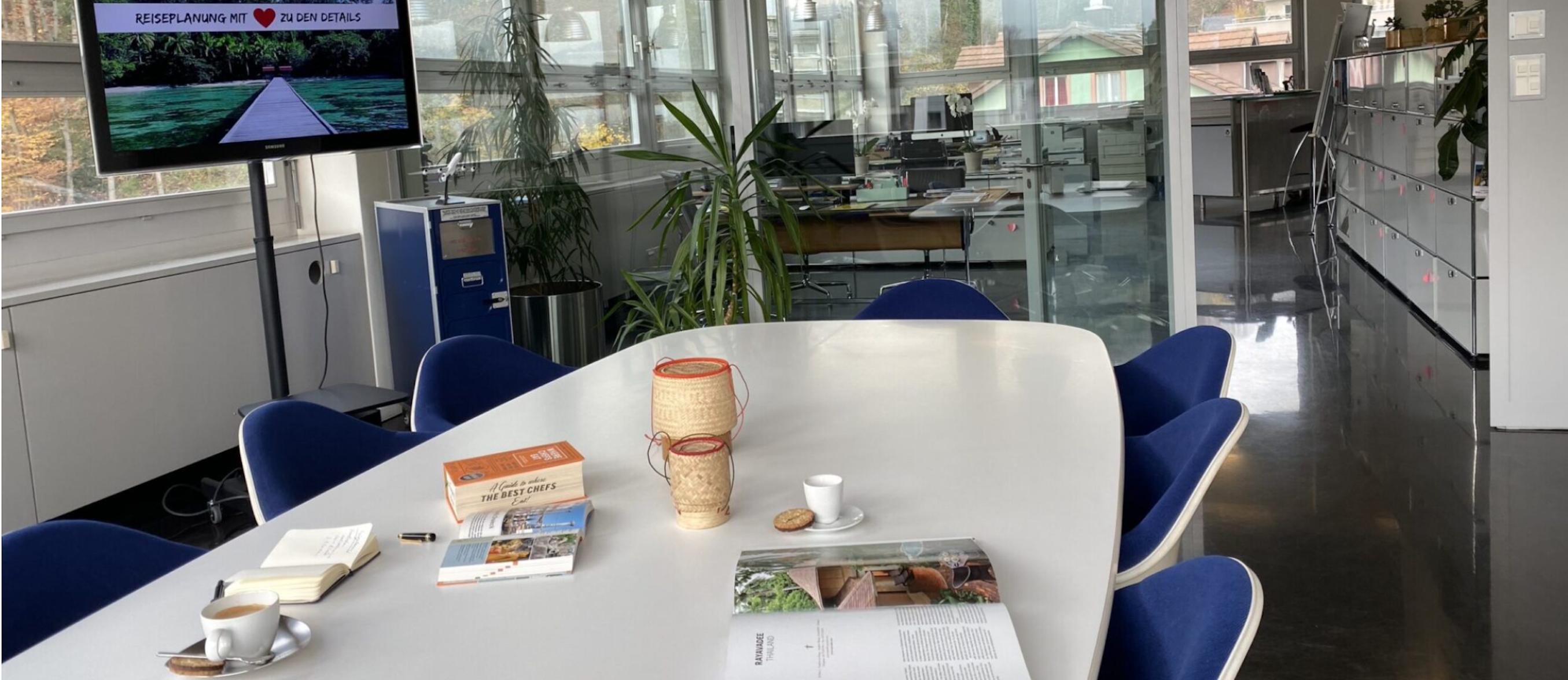 Das Reisebüro Simtis in Baden ist modern eingerichtet, auf dem Tisch im Sitzungszimmer liegen Reiseführer und Reisezubehör drapiert, sowie zwei Tassen Kaffee.