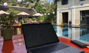 Ein Laptop steht auf einem roten Tisch, daneben liegt eine Powerbank, im Hintergrund liegt ein grosser Swimmingpool