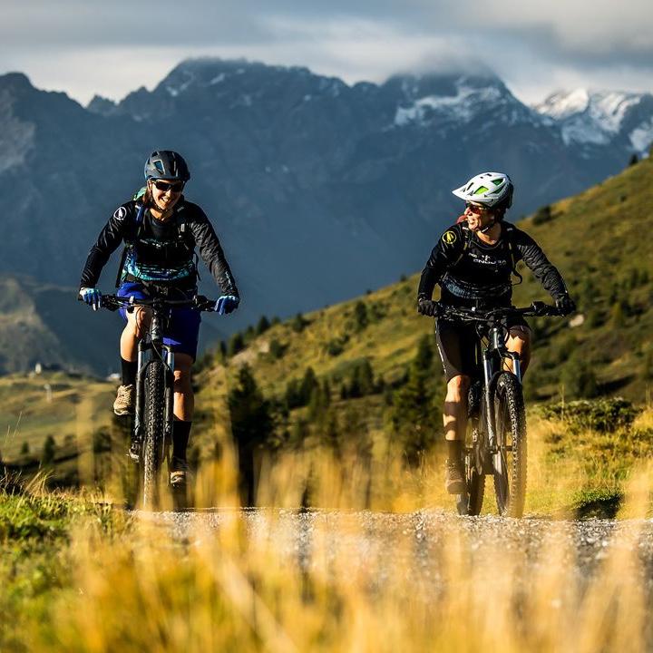 Reise in der Schweiz in Europa. Zwei Menschen fahren auf Mountainbikes eine Schotterstrasse entlang, umgeben von hohen Bergen.