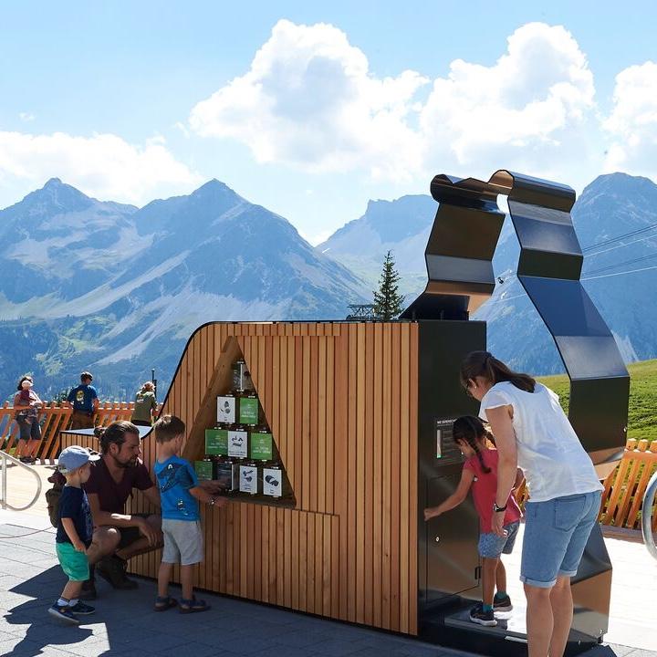 Reise in der Schweiz in Europa. Eine Familie (Eltern mit drei Kindern) untersucht einen Posten beim Bärenpark in Arosa, im Hintergrund ist das beeindruckende Panorama zu sehen.
