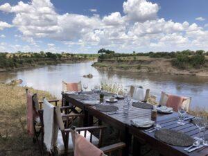 Reise in Tansania in Afrika. Ein langer, gedeckter Frühstückstisch steht am Ufer eines Flusses in der Serengeti Savanne.
