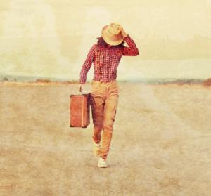 Reisebild. Frau trägt rote Bluse, braune Hosen und beigen hut mit Krempel. Sie hält den Hut fest, trägt in der Hand einen Lederkoffer und läuft auf der Strasse. Sie ist auf dem Weg zu einer Reise.
